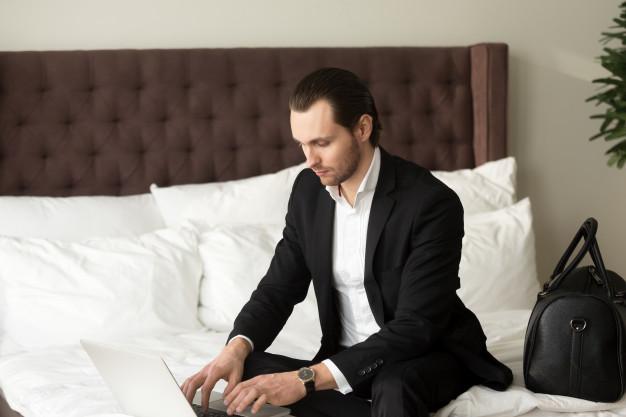 hombre-negocios-joven-que-sienta-cama-que-trabaja-computadora-portatil-hotel_1163-5504